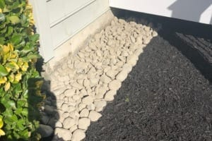 River rock installation around perimeter of house